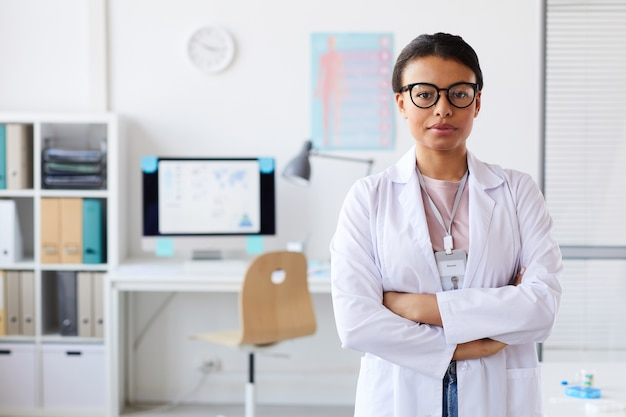 Portrait of young female doctor in eyeglasses standing with her arms crossed at office