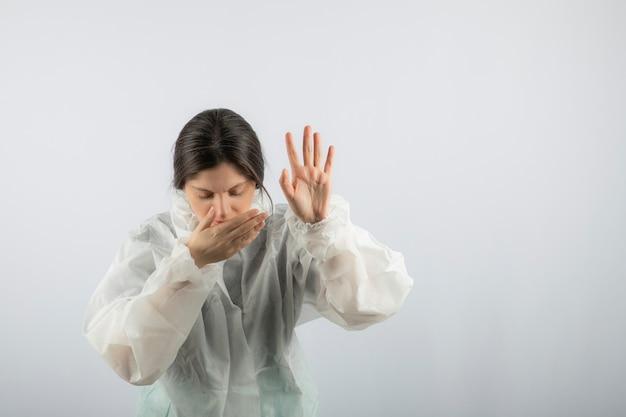 Ritratto di giovane donna scienziato medico in camice da laboratorio difensivo tosse.