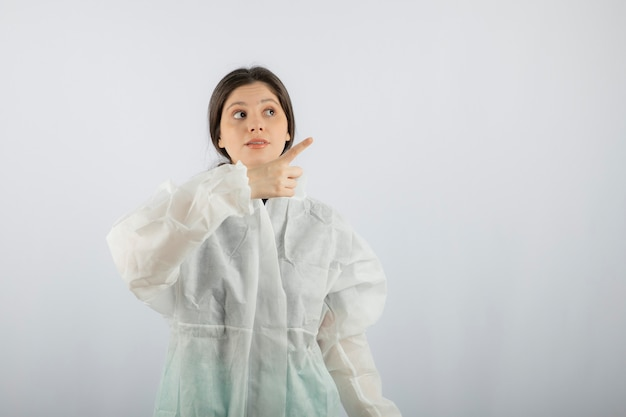 Portrait of young female doctor scientist in defensive lab coat pointing up.
