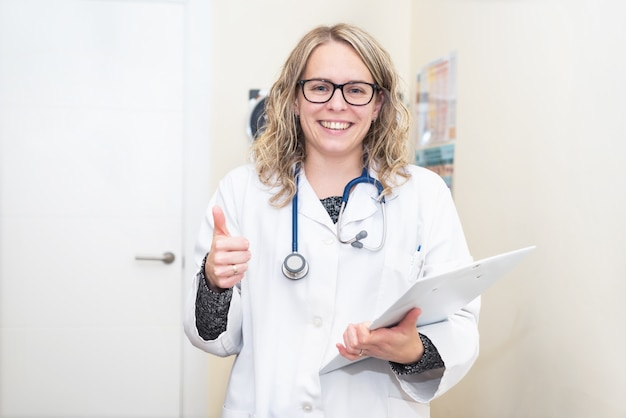 Portrait of a young female doctor showing thumbs up, positive emotion.