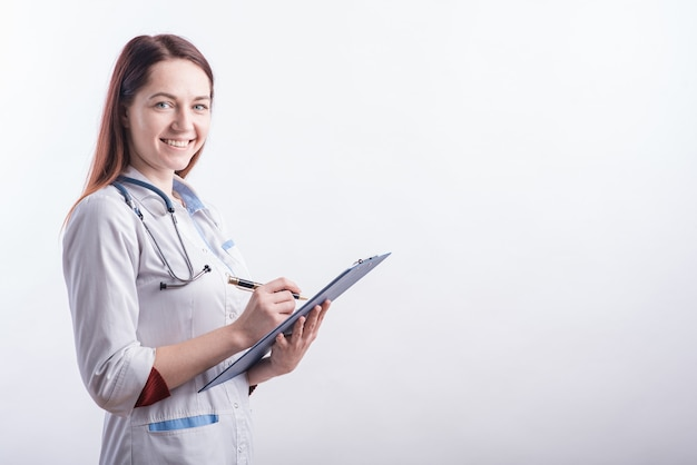Portrait of a young female doctor in a white uniform with a folder and a pen in hands in the studio on a white background with copyspace