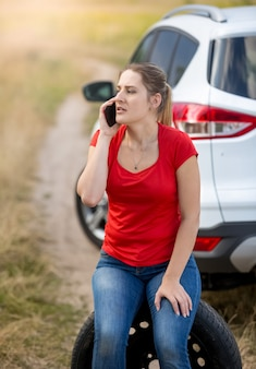 Portrait of young female driver sitting next broken car at field and talking by phone