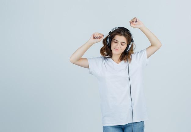 Ritratto di giovane donna che gode della musica con le cuffie in t-shirt bianca, jeans e guardando gioiosa vista frontale