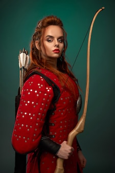 Portrait of young female fighter in red armor keeping dow and looking at camera in studio