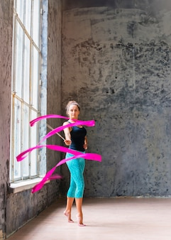Portrait of a young female gymnast dancer dancing with pink ribbon