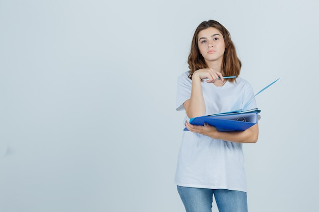 Portrait of young female holding folders and pen in white t-shirt, jeans and looking pensive front view