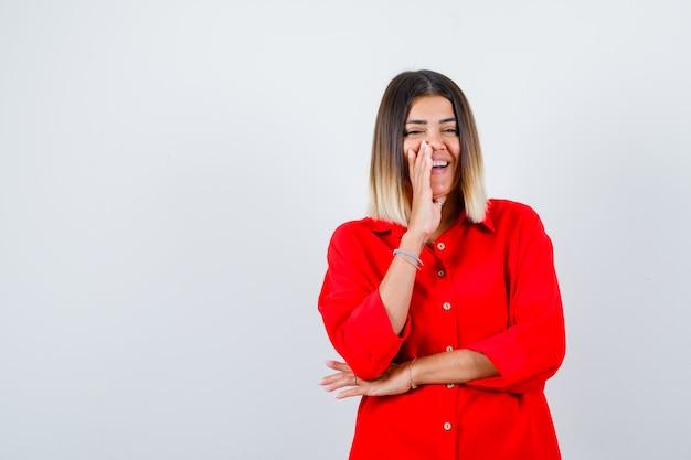 Ritratto di giovane donna che tiene la mano sulla guancia in una camicia rossa di grandi dimensioni e sembra una vista frontale allegra