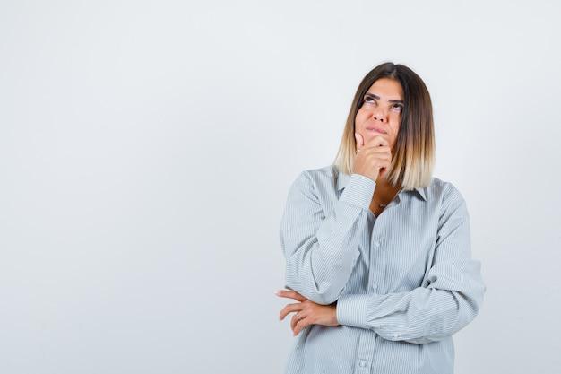 Ritratto di giovane donna che tiene la mano sul mento in camicia oversize e guarda una vista frontale premurosa