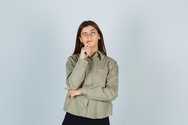 Ritratto di giovane donna che tiene la mano sul mento in camicia, gonna e guarda una vista frontale premurosa