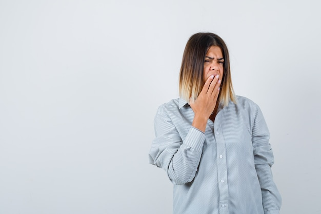 Portrait of young female holding hand on mouth in oversized shirt and looking anxious front view