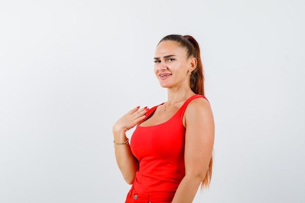 Ritratto di giovane donna che tiene la mano sulla spalla in canottiera rossa, pantaloni e guardando fiducioso vista frontale