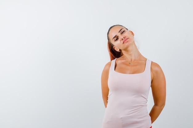 Ritratto di giovane donna che tiene le mani dietro la schiena in canottiera bianca e guardando affascinante vista frontale