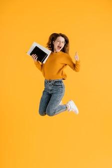 세로 젊은 여성 점프와 책을 들고
