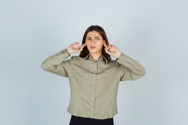 Ritratto di giovane donna che tiene le dita dietro le orecchie mentre si acciglia in camicia, gonna e guarda confusa vista frontale