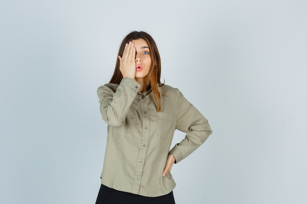 Ritratto di giovane donna che tiene la mano sull'occhio in camicia, gonna e guarda stupita vista frontale