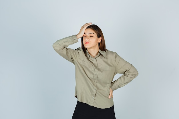 Ritratto di giovane donna che tiene la mano sulla testa in camicia, gonna e sembra stanca vista frontale