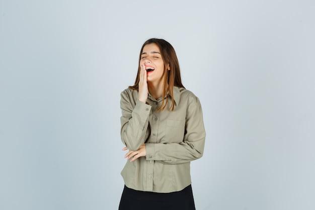 Ritratto di giovane donna mantenendo la mano sulla bocca mentre si ride in camicia