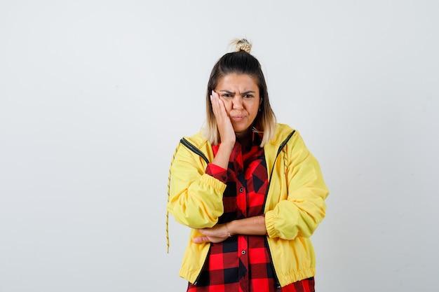 Ritratto di giovane donna che tiene il palmo sulla guancia in camicia a scacchi, giacca e sembra sconvolta vista frontale