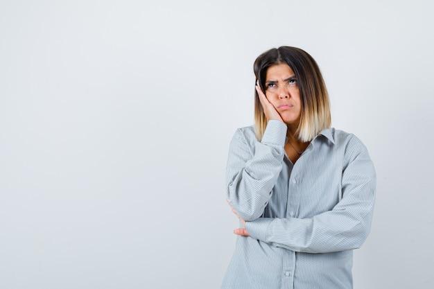 Ritratto di giovane donna con la guancia appoggiata a portata di mano in una camicia sovradimensionata e dall'aspetto pensieroso vista frontale