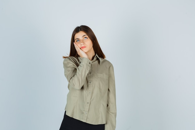 Portrait of young female leaning cheek on palm, looking up in shirt, skirt and looking hopeful front view