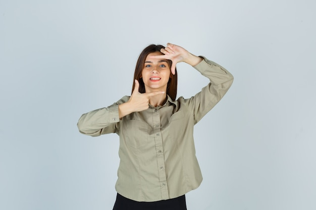 Portrait of young female making frame gesture in shirt, skirt and looking happy front view