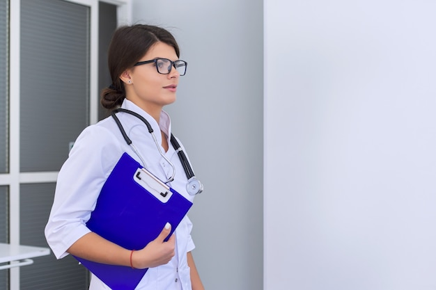 Portrait of young female medical doctor with stethoscope clipboard at hospital