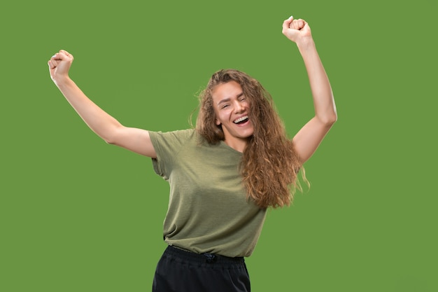 Ritratto di giovane modello femminile che balla isolato sulla parete verde