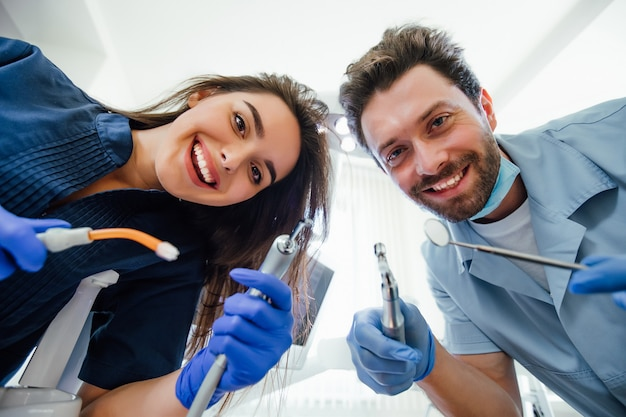 Portrait of a young female nurse and dentist doctor wearing a blue coat posing in a dentist office with medical equipment.