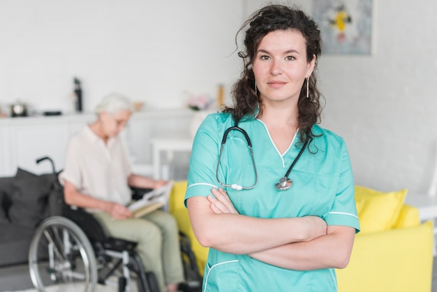 Portrait of young female nurse standing in front of senior woman sitting on wheel chair