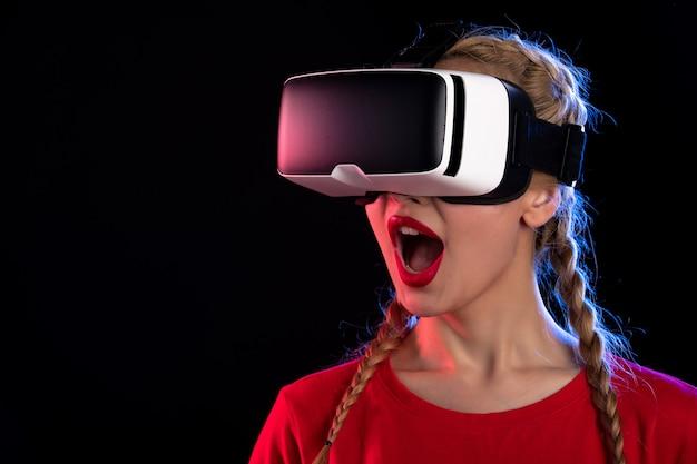 Ritratto di giovane donna che gioca con la realtà virtuale sul gioco ad ultrasuoni visivo scuro d