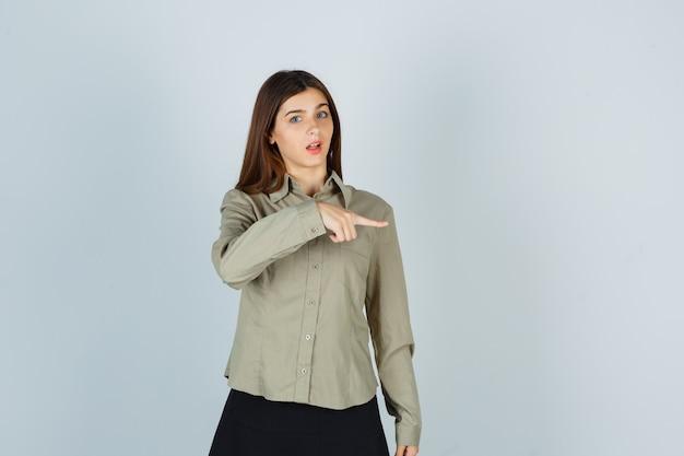 Ritratto di giovane donna che punta a destra in camicia, gonna e guarda la vista frontale meravigliata