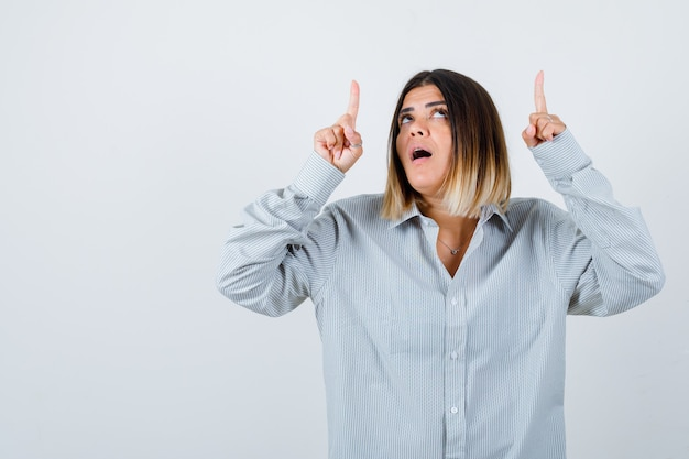 Ritratto di giovane donna che punta verso l'alto in una camicia oversize e guarda perplessa vista frontale