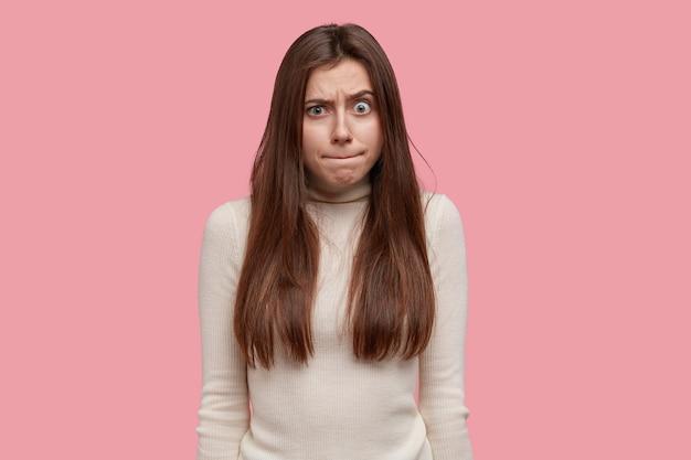 Ritratto di giovane donna preme le labbra e si sente sconvolta e stupita, solleva le sopracciglia, essendo sotto tensione o pressione