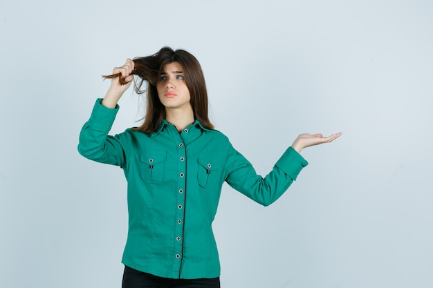 Portrait of young female pulling her hair, spreading palm aside in green shirt and looking disappointed front view