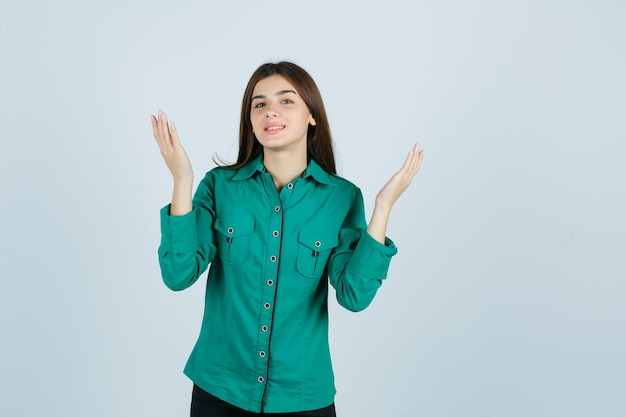 Ritratto di giovane donna che solleva le mani mentre sorride in camicia verde e guarda speranza vista frontale