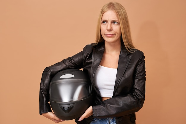 Portrait of young female rider with teeth braces and long straight hair posing isolated in black leather jacket