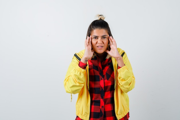 Portrait of young female rubbing temples in checkered shirt, jacket and looking happy front view
