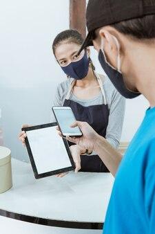 肖像画の若い女性の店主は、健康的なプロトコルで顧客のqrバーコードオンライン支払いを提供します