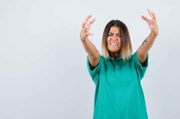 Ritratto di giovane donna che mostra artigli che imitano un gatto con una t-shirt polo e che sembrano vista frontale aggressiva