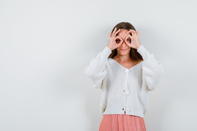 Ritratto di giovane donna che mostra gesto di occhiali in cardigan isolato