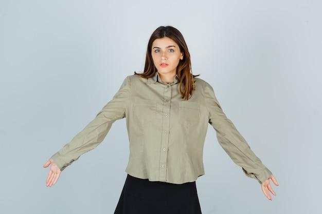 Ritratto di giovane donna che mostra gesto impotente allargando le braccia in camicia