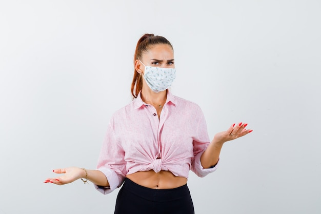 Portrait of young female showing helpless gesture in shirt, pants, medical mask and looking serious front view