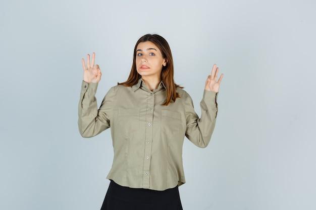 Ritratto di giovane donna che mostra gesto giusto in camicia, gonna e sguardo confuso