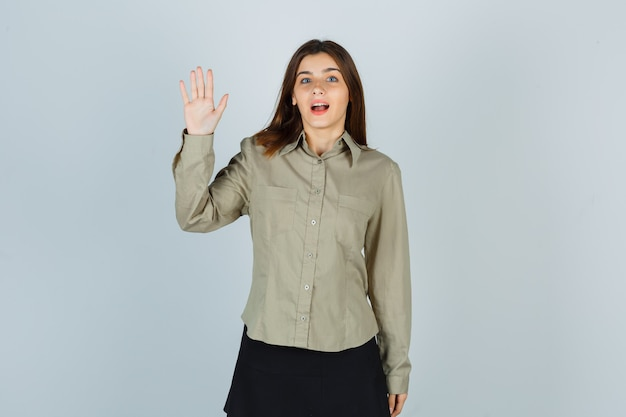 Ritratto di giovane donna che mostra la palma in camicia, gonna e guardando la vista frontale