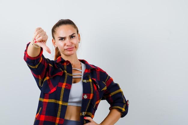 Ritratto di giovane donna che mostra il pollice verso il basso in crop top, camicia a scacchi e guardando dispiaciuto vista frontale