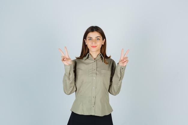 Ritratto di giovane donna che mostra il gesto di vittoria in camicia, gonna e guardando fiducioso