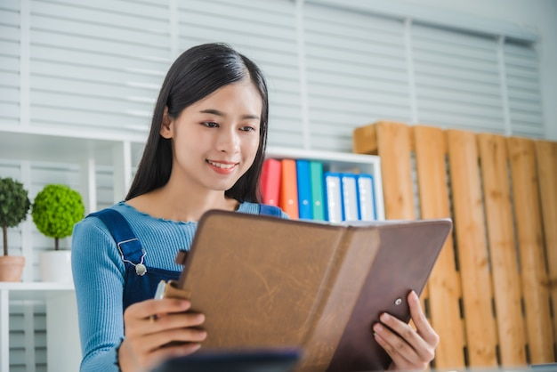 Portrait of young female smile charming lady with notebook paper, attractive asian woman feeling happy.