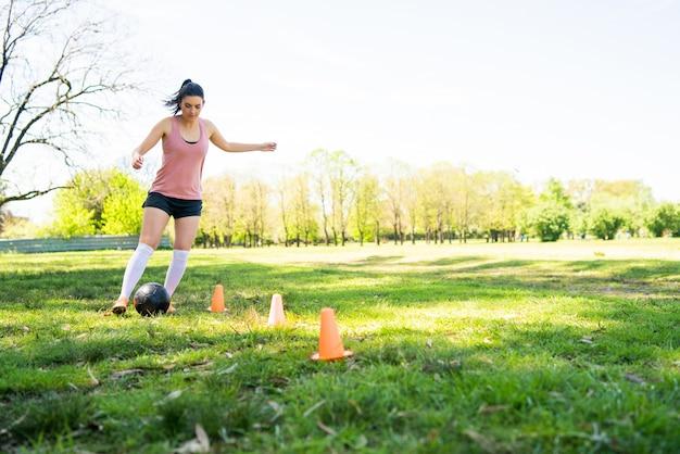 Ritratto di giovane calciatore femminile che corre intorno ai coni mentre si esercita con la palla sul campo