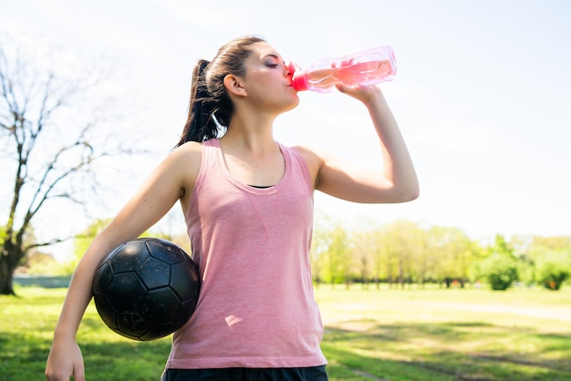 Portrait of young female soccer player taking break on pitch and drinking water from bottle