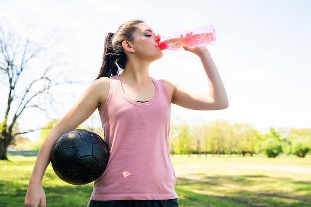 Ritratto di giovane calciatore femminile prendendo pausa sul campo e acqua potabile dalla bottiglia